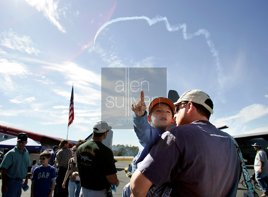 Walker White, 3, looks around The Great Georgia Airshow with his father, Jeff as a stunt plane performs a maneuver at Falcon Field Airport in Peachtree City, Ga. on Sunday, Oct. 15, 2006.<br />