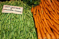 Carrots and beans on display with funny sign