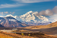 Tourists on buses stop at the Stoney Dome lookout to view the massive Mt Denali, visible in the distance, Denali National Park, interior, Alaska.