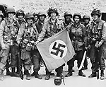 American paratroopers, proudly display a Nazi flag captured after they made a successful landing behind the German lines on the Normandy coast of France on June 9, 1944. (AP Photo)