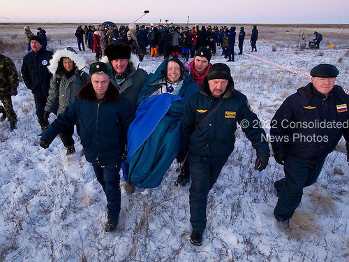 Expedition 29 Commander Mike Fossum smiles as he is carried in a chair to the medical tent just minutes after he and Expedition 29 Flight Engineers Sergei Volkov and Satoshi Furukawa landed in a remote area outside of the town of Arkalyk, Kazakhstan, on Tuesday, November 22, 2011. NASA Astronaut Fossum, Russian Cosmonaut Volkov and JAXA (Japan Aerospace Exploration Agency) Astronaut Furukawa are returning from more than five months onboard the International Space Station where they served as members of the Expedition 28 and 29 crews. .Mandatory Credit: Bill Ingalls / NASA via CNP