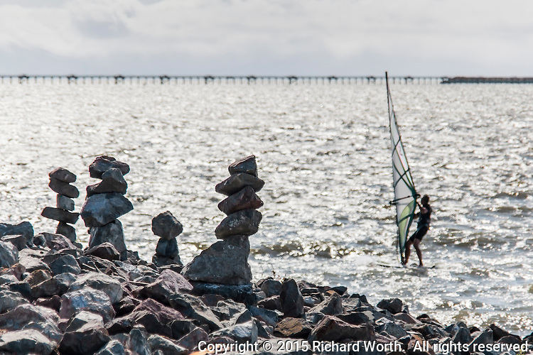 A windsurfer rides the choppy waters of San Francisco Bay.  On the shore, ad hoc sculpture, 'rock balancing' creations along the San Leandro Marina shores.  In the background, the approach to the Oakland's International Airport.
