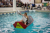 "Vera Linani, a freshman, center, pilots her team's boat in the Brooklyn Technical High School Cardboard Boat Regatta in the school's pool in Brooklyn in New York on Friday, March 1, 2013. As part of Engineering Week the teams of students constructed boats made only of cardboard and duct tape. The team's assigned ""captain"" piloted their boat from one end of the pool to the other and back in a heat with other boats, hopefully without sinking. The surviving boats were timed and the winners received bragging rights with an award also going to the most spectacular sinking. (© Richard B. Levine)"