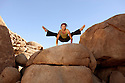 Free spirited man practicing hatha yoga posture titibasana on some giant rocks.