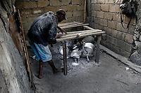 A Haitian man polishing an aluminium pot in the aluminium recycling shop on the street of Port-au-Prince, Haiti, 11 July 2008.