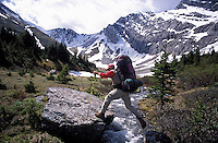 CANADA, ALBERTA, KANANASKIS, MAY 2002. A Hiker jumps over a mountain stream near Paradise pass. The Kananaskis Country provincial park is home to Canada's most beautiful nature and wildlife. It has also escaped the mass tourism as in Banff National Park. Photo by Frits Meyst/Adventure4ever.com