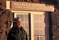 A Haleakala National park ranger stands next to the Haleakala Visitor Center sign after sunrise.
