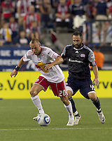 New York Red Bulls midfielder Joel Lindpere (20) controls the ball as New England Revolution defender Ryan Cochrane (45) defends. In a Major League Soccer (MLS) match, the New England Revolution tied New York Red Bulls, 2-2, at Gillette Stadium on August 20, 2011.