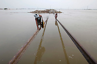 Flood victims use a part of a damaged railway track to cross the floodwaters toward a village in Sultan Kot, about 51 km (31 miles) from Sukkur in Pakistan's Sindh province August 31, 2010. A month after torrential monsoon rains triggered Pakistan's worst natural disaster on record, flood waters are starting to recede -- but there are countless survivors at risk of death from hunger and disease. REUTERS/Damir Sagolj (PAKISTAN)