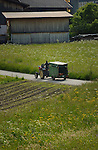Tractor pulling trailer along country lane, Imst district, Tyrol/Tirol, Austria, Alps.