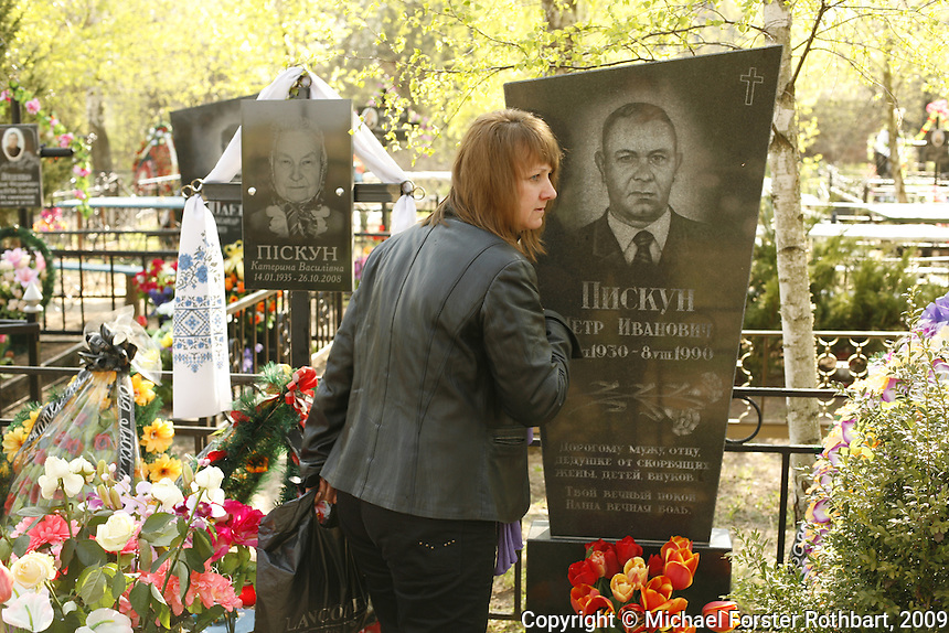 On April 26, the anniversary of the Chernobyl accident, Lena Kurilenko visits her parents&rsquo; graves in the Pirogovichi village graveyard. Ukrainians traditionally return to their hometowns around Easter to gather and honor their dead. <br /> ------------------- <br /> This photograph is part the book of Would You Stay?, by Michael Forster Rothbart, published by TED Books in 2013. The photos come from Forster Rothbart&rsquo;s two long-term documentary photography projects, After Chernobyl and After Fukushima.<br /> &copy; Michael Forster Rothbart 2007-2013.<br /> www.afterchernobyl.com<br /> www.mfrphoto.com &bull; 607-267-4893 &bull; 607-436-2856 <br /> 34 Spruce St, Oneonta, NY 13820<br /> 86 Three Mile Pond Rd, Vassalboro, ME 04989<br /> info@mfrphoto.com<br /> Photo by: Michael Forster Rothbart<br /> Date:  4/2009    File#:  Canon 5D digital camera frame 61520