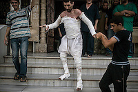 In this Sunday, Sep. 22, 2013 photo, a Syrian man whom survived with 60% of his body burned during an airstrike is helped to walk down stairs in his way back to home at the field hospital in Kafr Zita, a village turned into a battlefield where clashes between troops loyal to president Bashar Al-Assad and opposition fighters have broken out as many opposition armed groups have launched a coordinated attack over the Syrian army positions in the Idlib province countryside, Syria. (Photo/AP).