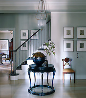 The entrance hall is furnished with a Chinese table and a Russian mahogany chair and a 19th century French pendant light