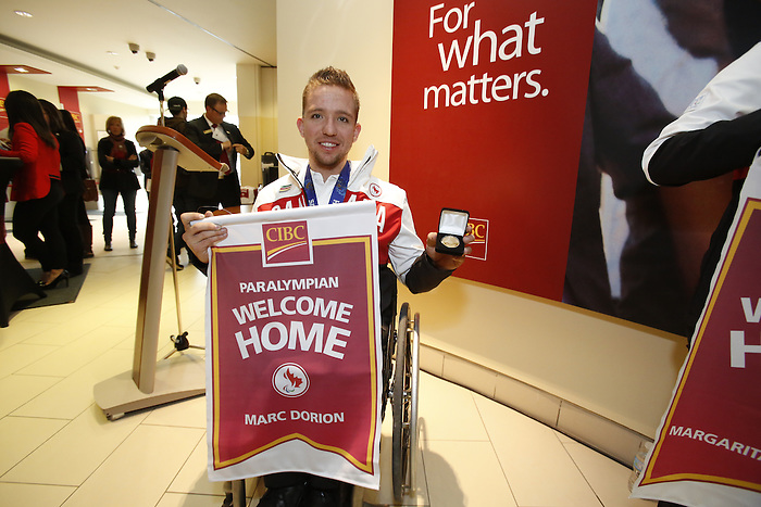 Ottawa, ON - March 28 2014- Sochi 2014 Paralympic Games bronze medallist Marc Dorion of the sledge hockey team displays his limited edition gold-plated coin and personalized Welcome Home banner at the CIBC Paralympic Welcome Home Event at CIBC South Keys Banking Centre in Ottawa (Photo: Patrick Doyle/CIBC)