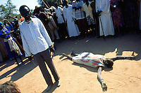 Sudan. South Sudan. Bahr El Ghazal. Mayen Abun. Crowd celebrating the visit of SPLA ( Sudanese People Liberation Army) commandant Salva, Chief of General Staff.  Man lying on the ground wears a dress made out of a corn bag from the WFP (World Food Programm).  © 1999 Didier Ruef