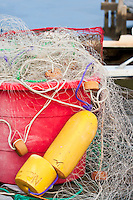 Buoys and fishing net piled in a red tub on a dock along Currituck Sound.