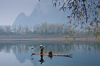 Fisherman in Suoyi coat and coolie hat fishes with cormorants on Li River near Guilin, China