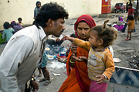 30 year old Buddhi Lal eats jam from his baby's finger in Karol Bagh, New Delhi.