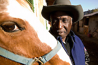 2 December 2006 - New York City, NY - Doctor D, a member of the Federation of Black Cowboys, looks at his horse at the Cedar Lanes stables in the borough of Queens in New York City, USA, 2 December 2006. The Federation gathers black men and women who recreate the heritage of black cowboys, teach kids to ride and put on 'rodeo showdeos'.