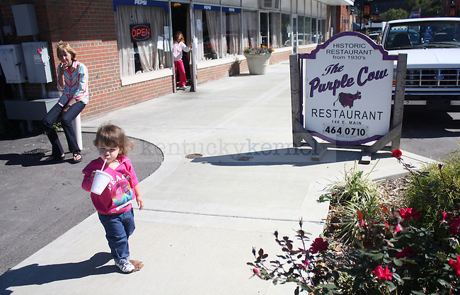 Nina Million sits outside of her restaurant, The Purple Cow, smoking a cigarette and watching her great-granddaughter, Kelli. Photo by Grace Profancik