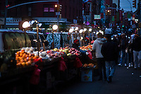 People cross by fruits displayed for customers at Manhattan's Chinatown in New York, Nov 11, 2013. VIEWpress/Eduardo Munoz Alvarez