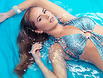Beauty portrait of young woman in blue swimsuit lying in water