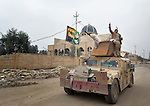 Iraqi soldiers--flying a Shia Muslim flag--patrol the street in front of a Syriac Orthodox Church in Mosul, Iraq, on January 27, 2017. The city was occupied by the Islamic State group in 2014 and partially liberated by the Iraqi army in early 2017. During their occupation, ISIS painted the front of the church with Islamist slogans, and used the building as a warehouse. According to neighbors, in the final weeks of their rule ISIS leaders sold the building to a contractor who began to demolish it in order to salvage the steel rebar in the walls. Although this portion of the city has been liberated, Christians are unlikely to return soon due to concerns about their security. And with Shia units of the military in control of the largely Sunni community, many expect Muslim rivalries will sooner or later plunge Mosul back into chaos.