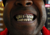 Abdur Rasheed Mumin displays his diamond cut removable gold grill at his store, Off Da Hook, on Water Avenue in Selma, Ala.  Some states have outlawed grill manufacturing in recent years.  Alabama law indicates grill vendors cannot cement or permanently install a grill or cause any permanent damage to the teeth.  Grill vendors that do not adhere to the law are charged with practicing dentistry without a license, which is a felony.