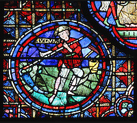 A peasant, wearing a hat to protect him from the sun and split trousers to prevent them getting caught, cuts the hay with a scythe. His sharpening stone and hoe lie in a basket. Section of June from the Zodiac and the labours of the months stained glass window, 1217, in the ambulatory of Chartres Cathedral, Eure-et-Loir, France. This calendar window contains scenes showing the zodiacal symbol with its corresponding monthly activity. Chartres cathedral was built 1194-1250 and is a fine example of Gothic architecture. Most of its windows date from 1205-40 although a few earlier 12th century examples are also intact. It was declared a UNESCO World Heritage Site in 1979. Picture by Manuel Cohen