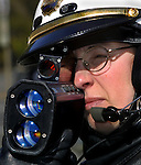 Cari Phebus, a motorcycle officer with the Portland Police Dept., trains her radar gun on speeders along Highway 30 in Linton. The speed limit drops from 45 to 35 but many drivers fail to slow down.