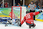 Billy Bridges (18) tries to get the puck past the Itialian goaltender during 3rd period action at a sledge hoceky game in Vancouver at the Paralympic Games. Credit: CPC/HC/Matthew Manor.