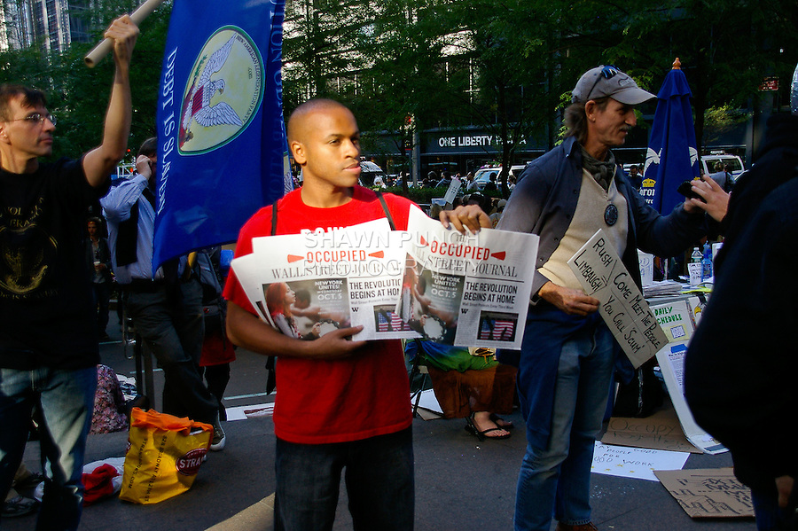 "Man hands out ""Occupied Wall Street Journal"" paper during the Occupy Wall Street Protest in New York City October 6, 2011."