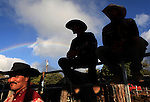 Bull riders wait their turn to participate in the bull riding event at the 4th of July Makawao Rodeo which is held annually at the Oskie Rice Arena in Olinda, upcountry Maui. Overhead a rainbow arcs across the sky.