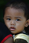 A boy rests his head on his mother's shoulder in A Luoi, Vietnam. April 25, 2013.
