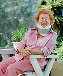 Senior woman sitting on deck chair, wearing neck brace, portrait