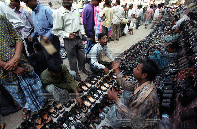 Shoe vendors sell cheap shoes on the pavement.