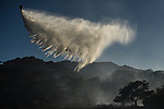 A helicopter from the Andalusian Service firefighting (INFOCA) drops water over scrub land during a forest fire in Los Barrios, near Cadiz on July 25, 2015. Since July 19 wildfires have ravaged nearly 39,000 hectares of land in Spain, according to the provisional figures from the agriculture ministry. © Pedro ARMESTRE