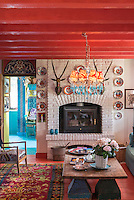 The atmosphere in this cosy sitting room is enhanced by its red-painted beamed ceiling