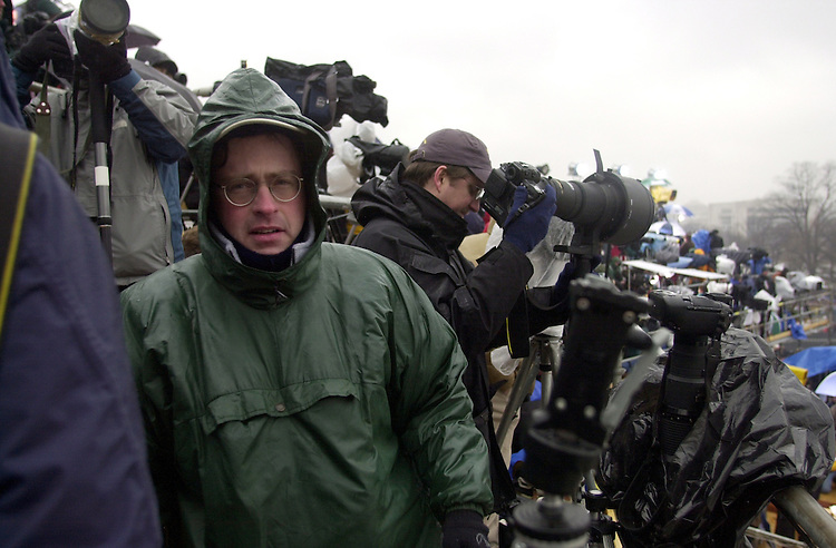Scott Ferrell Staff Photographer with Congressional Quarterly Magazine endures the rain along with the rest of the media during the 2001 Inauguration of George W. Bush for his first term as President of the United States.