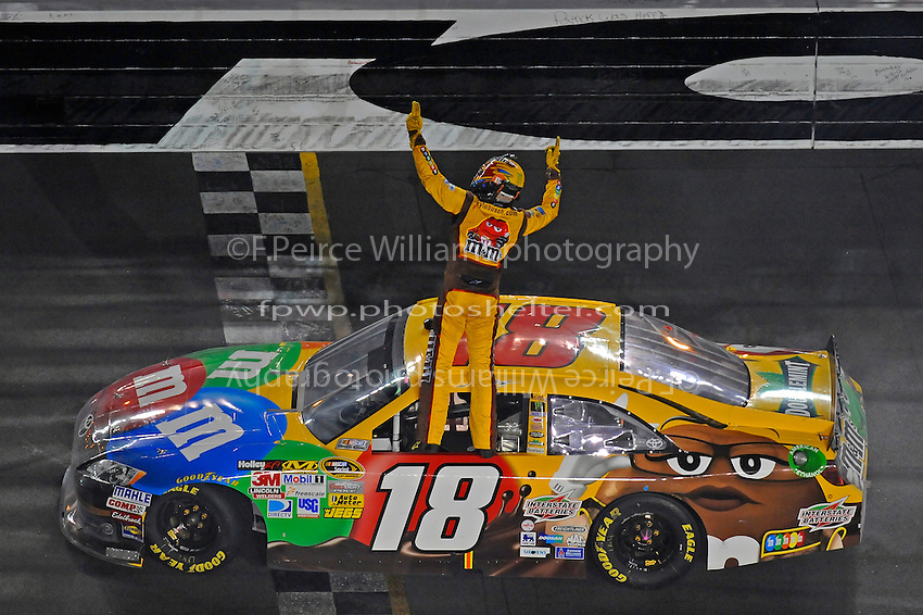 Winner Kyle Busch (#18) waves to the crowd from atop his car.