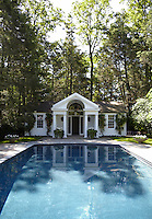 A classical poolhouse graces one end of the outdoor swimming pool