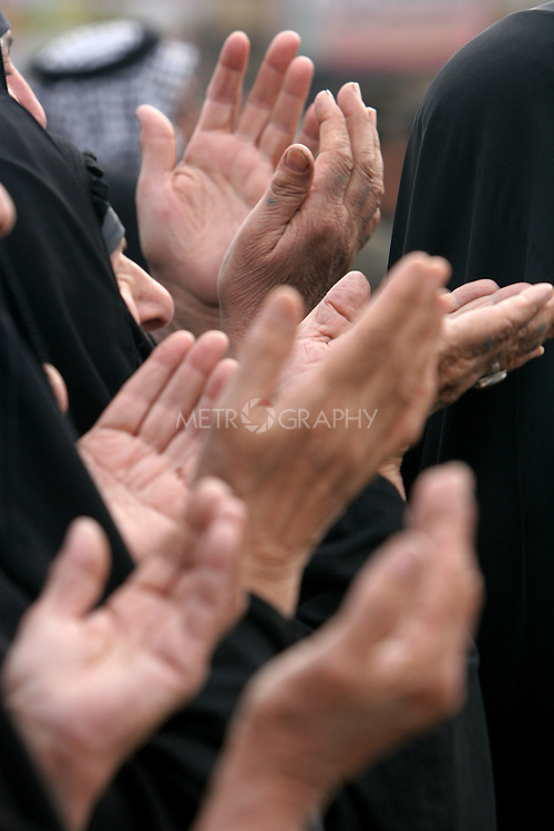 KARBALA, IRAQ: Shia pilgrims bring their hands up in prayer...Shia pilgrims pray during the last day of the Ashura festival...Photo by Metrography
