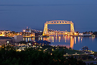 &quot;Aerial Lift Bridge Illumination&quot;<br /> <br /> Duluth's iconic Aerial Lift Bridge illuminates the stage during the evening twilight.<br /> <br /> The Aerial Lift Bridge is one of the most-recognized iconic landmarks of Duluth. In a mere 55 seconds, the bridge rises to 138 feet, making it the quickest and biggest lift bridge in the world.