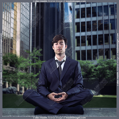 Conceptual portrait of a businessman in a suit meditating with downtown office buildings in the background. Meditation and busy life concept.