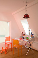 This child's bedroom is furnished with a simple desk and colourful Perspex chairs with a pendant light of Campari bottles by Ingo Maurer