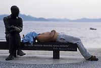 Man sleeps beside Brazilian poet Carlos Drummond de Andrade statue at Copacabana beach sidewalk, Rio de Janeiro, Brazil.