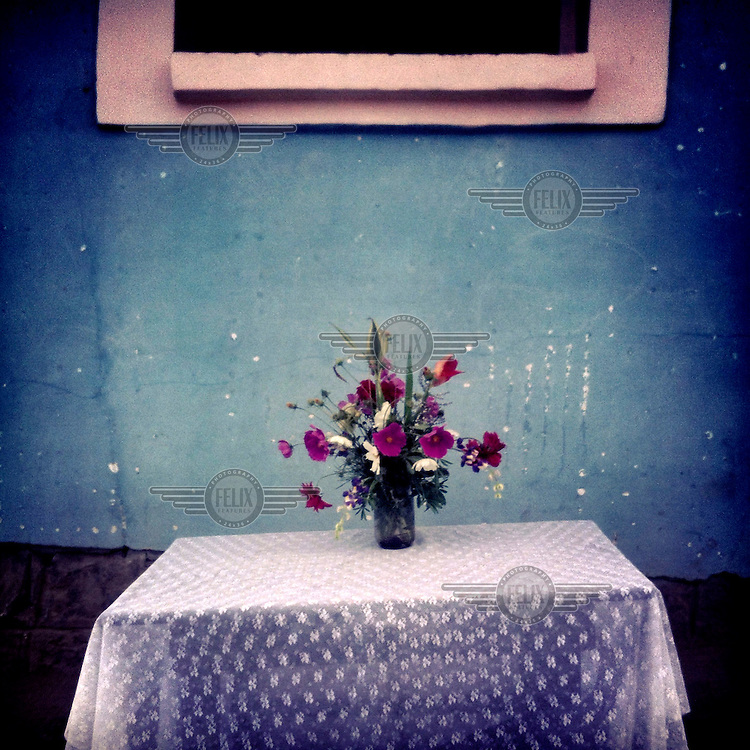 A bouquet of flowers sits on a table outside a house in Rumihuaico.