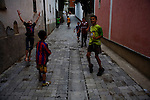Albanian kids celebrate a goal during a football match in a back alley of Mitrovica, Kosovo.