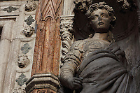 Allegory of Fortitude, one of the 4 Virtues, on the Porta della Carta, built 1438-42 by Bartolomeo and Giovanni Bon, entrance to the courtyard of the Doge's Palace or Palazzo Ducale, adjoining St Mark's Basilica or the Basilica San Marco, Venice, Italy. The gate was the main entrance to the palace, and where important announcements were posted to be read by the citizens of Venice. This was the residence of the Doge of Venice, the supreme authority of the former Republic of Venice, until the Napoleonic occupation in 1797, and is now a museum. The city of Venice is an archipelago of 117 small islands separated by canals and linked by bridges, in the Venetian Lagoon. The historical centre of Venice is listed as a UNESCO World Heritage Site. Picture by Manuel Cohen