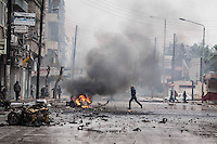 In this Monday, Dec. 17, 2012 photo, a man runs in panic among the debris of a shattered truck as smoke rises from a car in fire after a mortar shell landed on a commercial street killing two people in the Bustan Al-Qasr district of Aleppo, Syria. (AP Photo/Narciso Contreras)